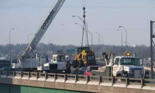 Crane moves skidloader off Interstate 380