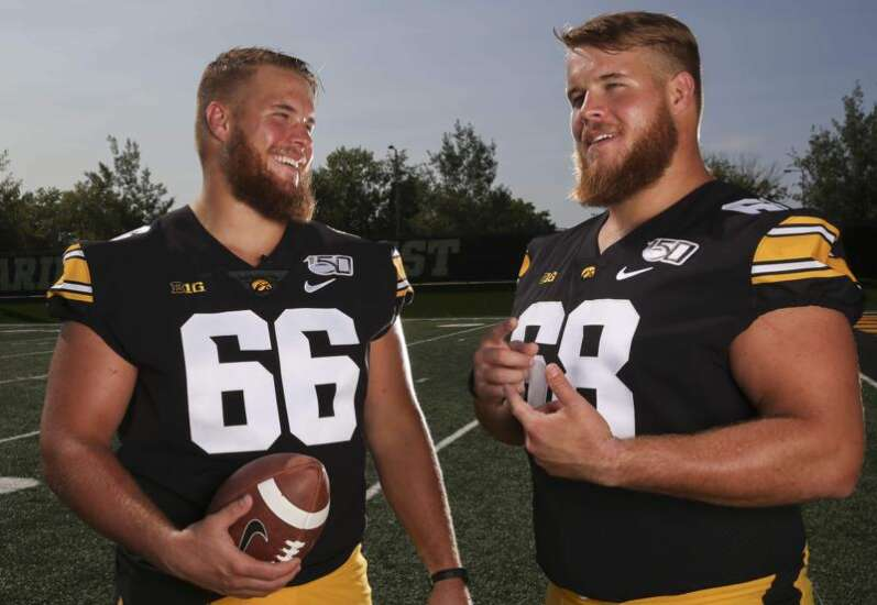 Iowa twins Levi and Landan Paulsen move couches, donate hair and guide young Hawkeyes together